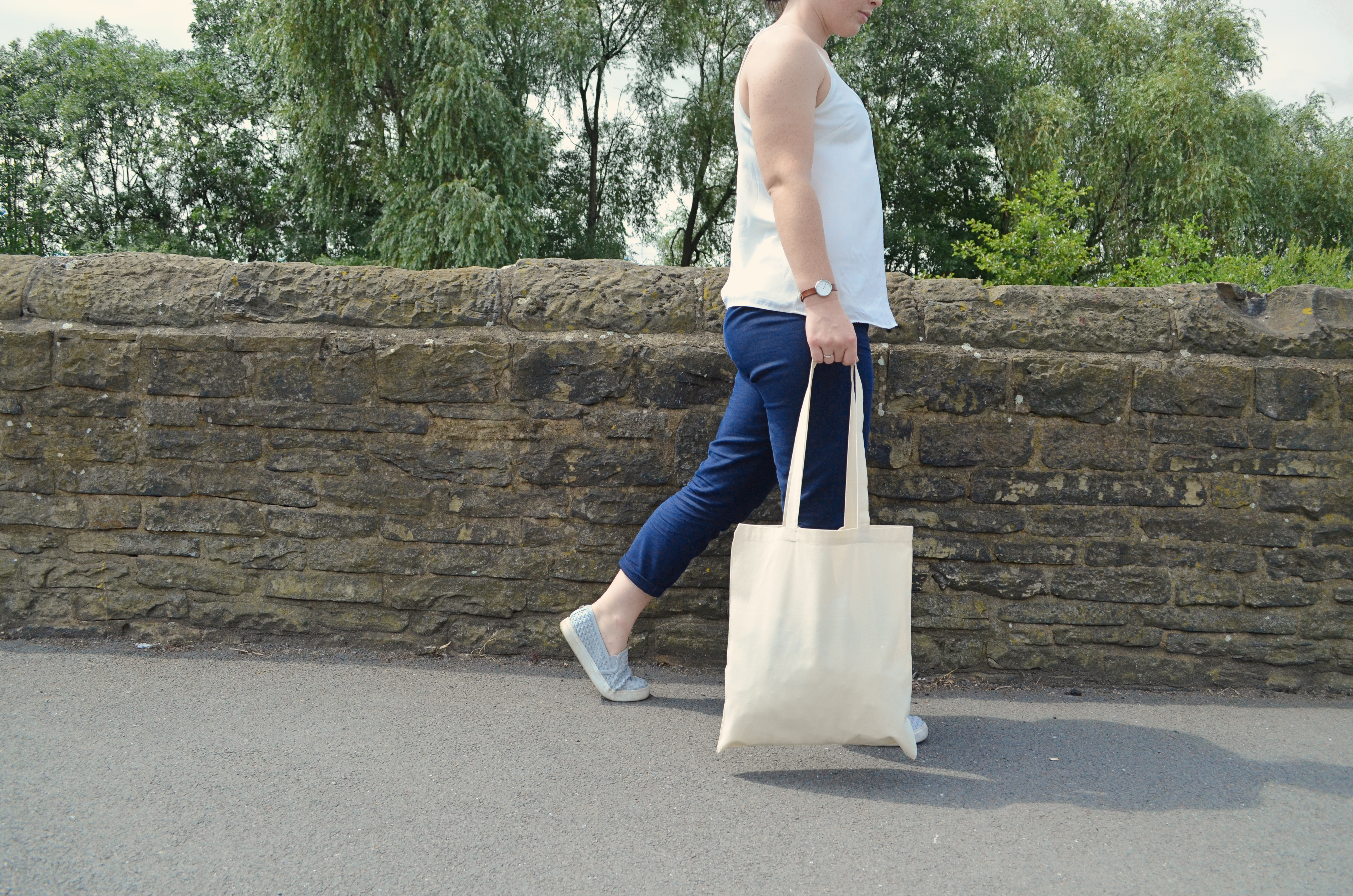 Woman holding a cotton tote bag while walking