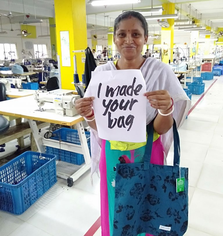 """Fairtrade worker holding a sign saying """"i made your bag"""""""
